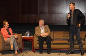 Gwen (left) on stage at a cancer summit with Lance (right). Time to pass the mic.